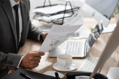 cropped view of trader holding papers with infographics near laptop and coffee cup