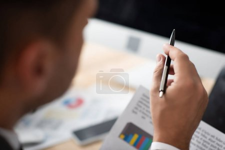 cropped view of trader pointing with pen on blurred foreground