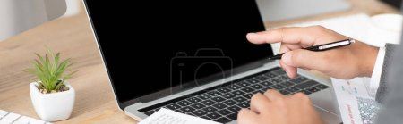 partial view of businessman pointing with finger at laptop, banner