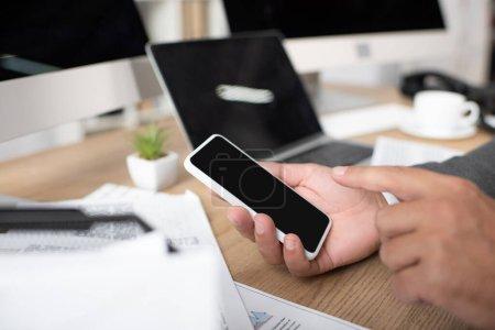 Photo pour Vue recadrée de l'homme d'affaires pointant du doigt le smartphone avec écran blanc, mise au point sélective - image libre de droit