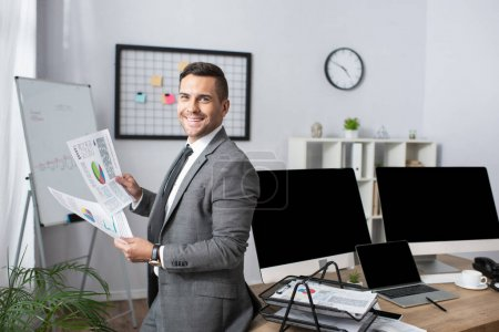comerciante sonriente celebración de infografías mientras está de pie cerca de monitores con pantalla en blanco