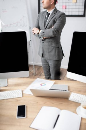 partial view of trader standing with crossed arms near laptop and monitors with blank screen