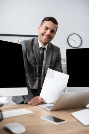 smiling trader looking at camera near computer monitors and laptop on blurred foreground