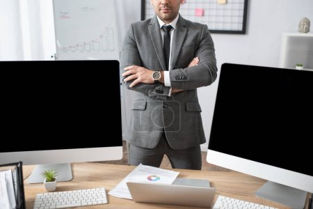 cropped view of trader standing with crossed arms near laptop and computer monitors