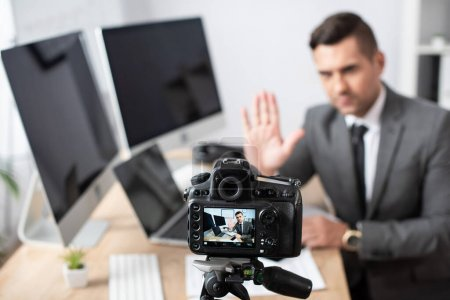 Photo for Selective focus of digital camera near trader waving hand on blurred background - Royalty Free Image