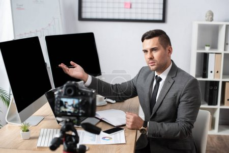 trader pointing with hand at computer monitors during online streaming on digital camera, blurred foreground