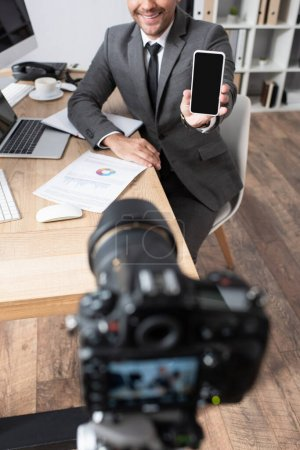 Photo for Cropped view of businessman showing mobile phone with blank screen near digital camera on blurred foreground - Royalty Free Image
