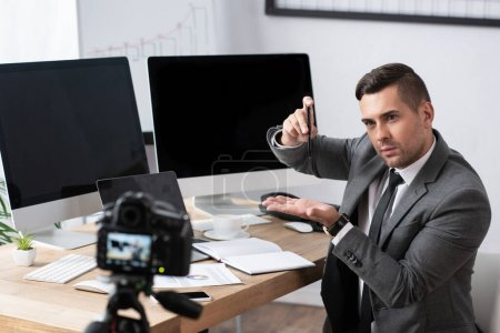 Photo for Trader demonstrating recession with pen during online streaming on digital camera, blurred foreground - Royalty Free Image