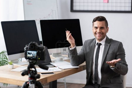 Photo for Smiling trader pointing with hand during video streaming on digital camera, blurred foreground - Royalty Free Image