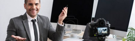 Photo for Cheerful trader sitting near monitors and pointing with hand during online streaming on digital camera, blurred foreground, banner - Royalty Free Image