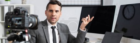 Photo for Businessman pointing with hand at computer monitors near digital camera on blurred background, banner - Royalty Free Image