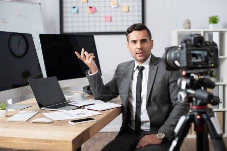Photo pour Trader financier pointant avec la main sur les moniteurs d'ordinateur en face de l'appareil photo numérique au premier plan flou - image libre de droit
