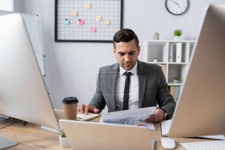 Photo pour Commerçant regardant le papier tout en étant assis près du café pour aller et les ordinateurs sur le premier plan flou - image libre de droit