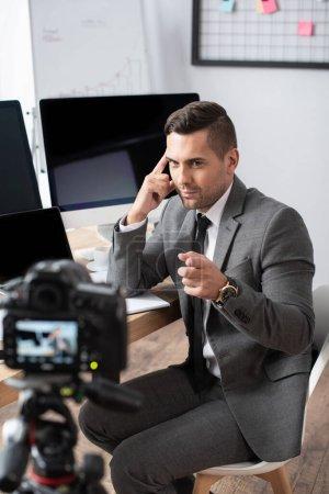 trader sitting near computer monitors and pointing with finger at digital camera