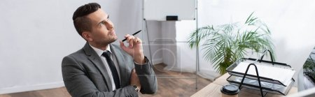 thoughtful trader holding pen and looking away at workplace in office, banner
