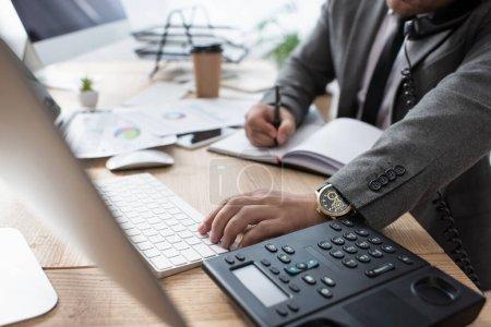Foto de Vista recortada del comerciante hablando por teléfono fijo, escribir en el cuaderno y escribir en el ordenador portátil, borrosa primer plano - Imagen libre de derechos