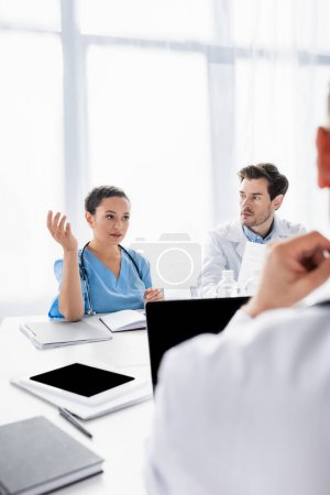 African american nurse talking to doctors near devices and notebooks on table