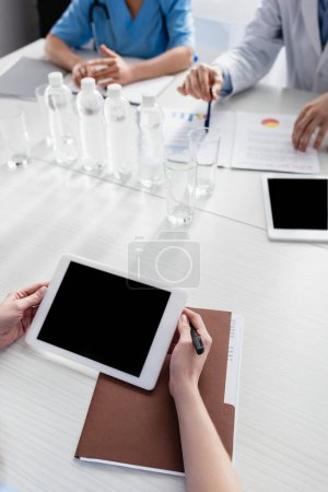 Cropped view of nurse holding digital tablet with blank screen near paper folder and colleagues on blurred background