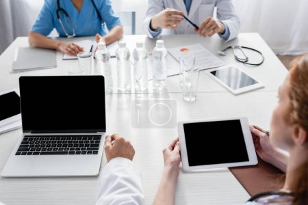 Photo for Devices with blank screen, water and papers on table near hospital staff on blurred background - Royalty Free Image