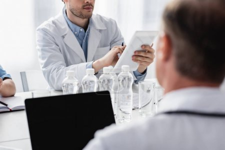 Cropped view of doctor using digital tablet near bottles of water and colleague on blurred foreground