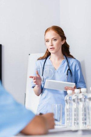 Krankenschwester zeigt mit Finger und hält digitales Tablet in der Nähe von Kollegen und Wasserflaschen im verschwommenen Vordergrund