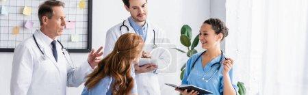 Photo pour Personnel hospitalier multiculturel avec tablette numérique et ordinateur portable travaillant en clinique, bannière - image libre de droit