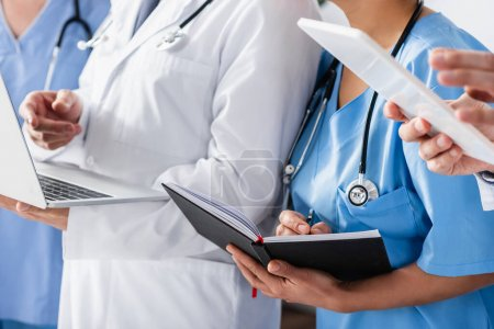 Cropped view of nurse writing on notebook near colleagues with devices on blurred background