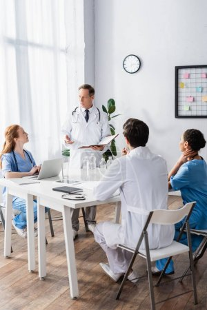 Doctor with paper folder pointing with hand near multiethnic colleagues and devices on table