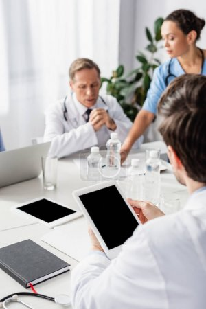 Digital tablet with blank screen in hands of doctor near multiethnic colleagues and devices on blurred background