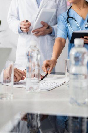 Cropped view of african american nurse pointing at papers near colleagues with digital tablet and bottles of water on blurred foreground