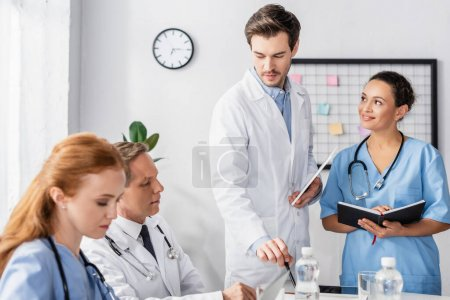 Photo for Multiethnic hospital staff with notebook and digital tablet working together in hospital - Royalty Free Image