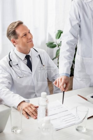Smiling doctor sitting near colleague pointing at papers and bottles of water on blurred foreground