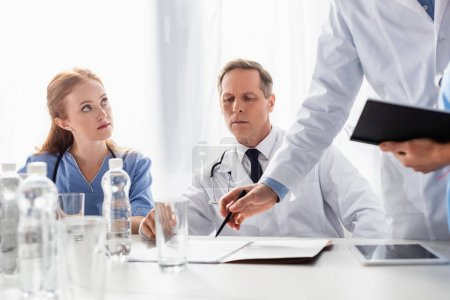 Photo for Doctor and nurse sitting near colleague pointing with hand at papers near bottles and digital tablet on blurred foreground - Royalty Free Image