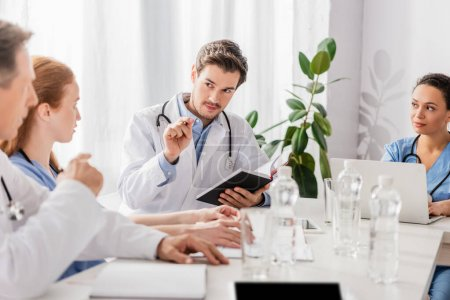 Photo for Doctor with notebook looking at colleagues near african american nurse with laptop in clinic - Royalty Free Image