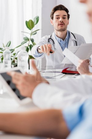 Doctor with papers pointing with finger near colleagues with digital tablet on blurred foreground