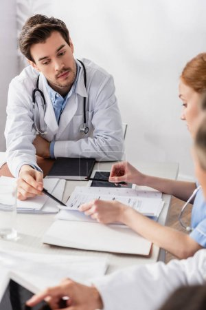 Doctor pointing at papers near digital tablet and nurse on blurred foreground