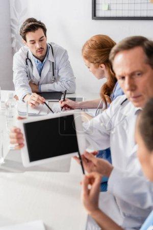Photo pour Médecin pointant vers les papiers près de l'infirmière et des collègues avec tablette numérique au premier plan flou - image libre de droit
