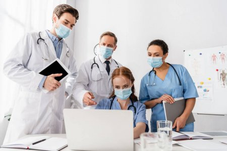 Photo for Multiethnic doctors and nurses in medical masks using laptop while working near papers on blurred foreground - Royalty Free Image