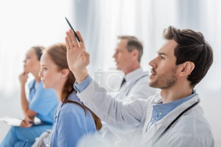 Doctor with raised hand near multiethnic colleagues during meeting in hospital on blurred background