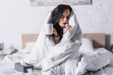 kranke junge brünette Frau mit Heißgetränk niest im Bett