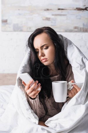 Photo for Sick young brunette woman with hot drink and tissue using smartphone in bed - Royalty Free Image