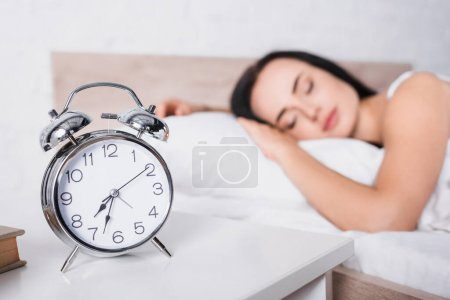 classic alarm clock and blurred young brunette woman sleeping in bed on background