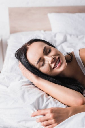 Photo for Smiling young brunette woman in bed - Royalty Free Image