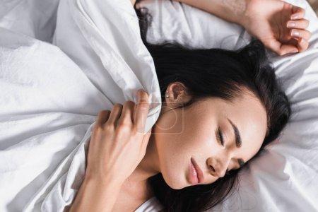 Photo pour Vue du dessus de la jeune femme brune au lit dormant sous la couverture - image libre de droit