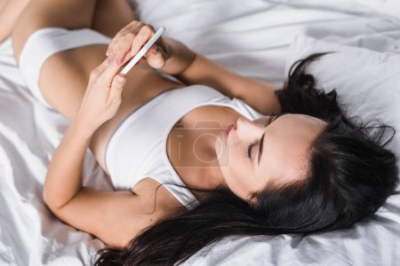Photo for Young brunette woman in bed using smartphone - Royalty Free Image