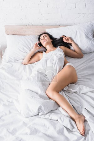 Photo for Smiling young brunette woman talking on smartphone in bed - Royalty Free Image