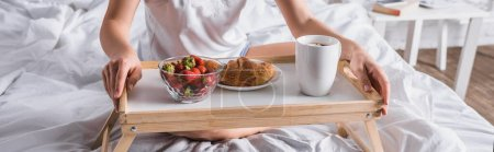 cropped view of young woman having croissant and strawberry for breakfast in bed, banner