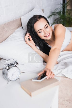 Photo for Young brunette woman in bed putting smartphone near alarm clock, blurred foreground - Royalty Free Image