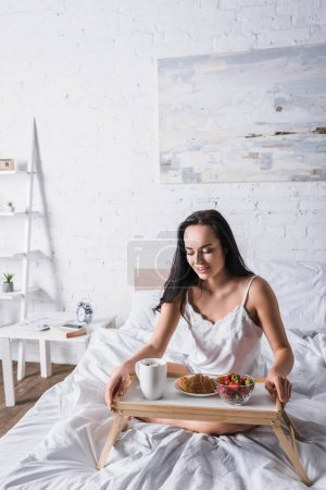 young brunette woman having croissant and strawberry for breakfast in bed