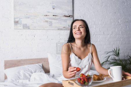 happy young brunette woman having croissant and strawberry for breakfast in bed